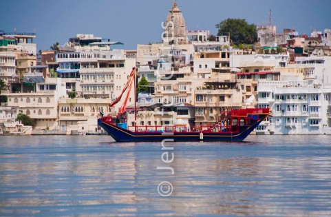 Udaipur's old city provides a backdrop for this decorative ship on Lake Pichola